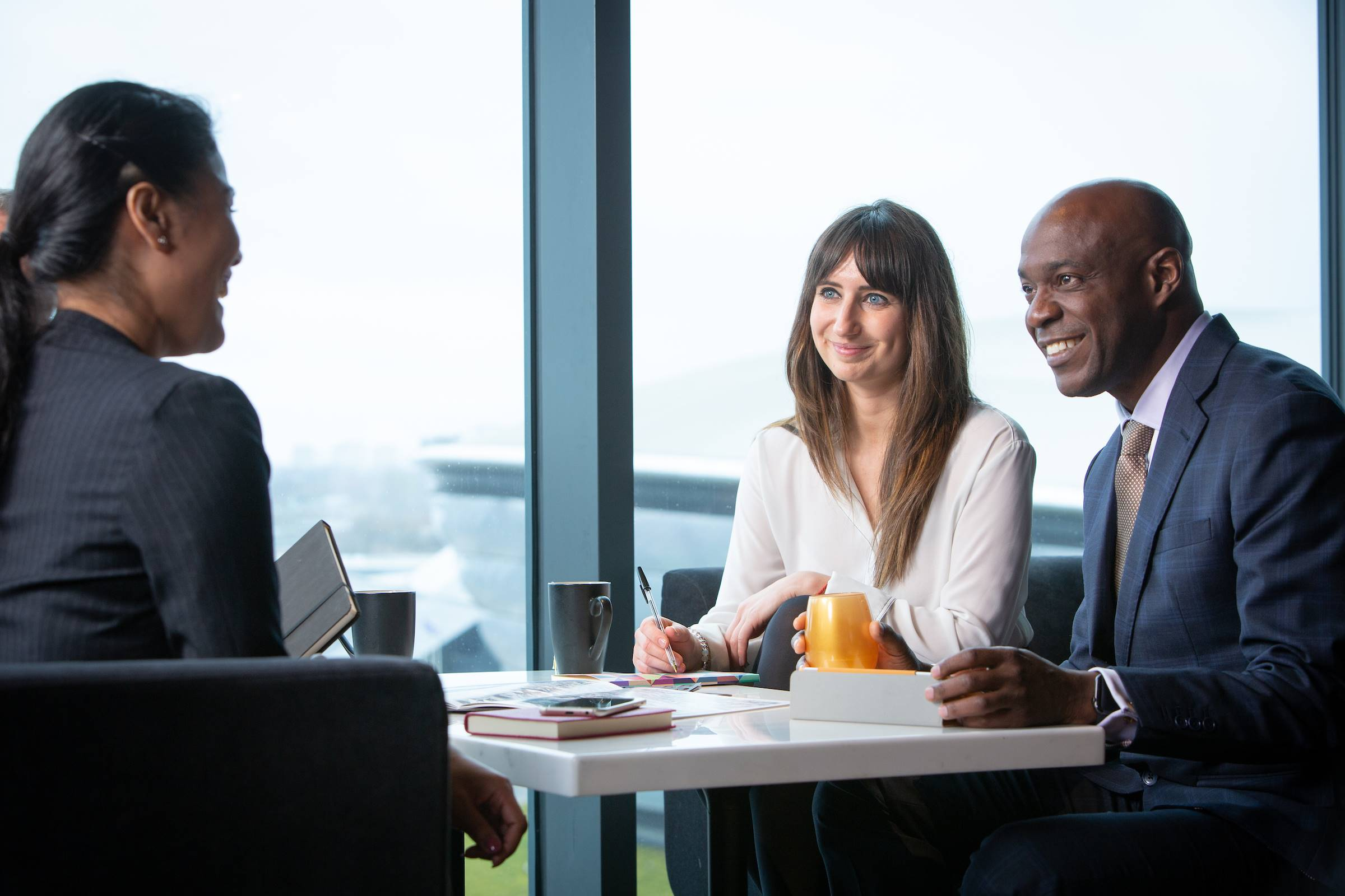 Three people sitting with coffee chatting business