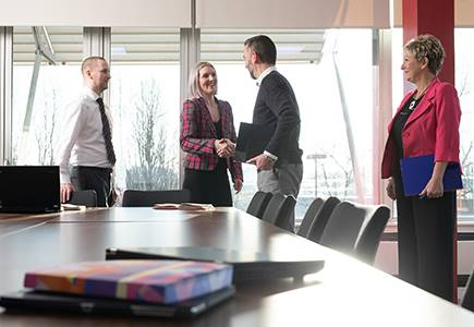 Staff and client shaking hands in meeting room